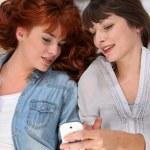 två kvinnor liggande med en mobiltelefon — Stockfoto #8920693