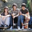 Three teen skateboarders sat on steps - Stock Photo