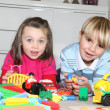 Brother and sister playing with toys - Stock Photo