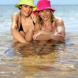 Two girlfriends bathing in the sea - Stock Photo