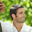Handsome man leaning against a tree — Stock Photo #8922970