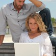 Couple with laptop outdoors — Stock Photo #8924128