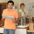 Young man reading a newspaper while his wife cooks dinner - Stock Photo