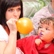 Mother inflating party balloon - Foto Stock