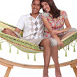 Happy couple sitting in a hammock - Stock Photo
