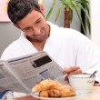 Man at kitchen table having breakfast — Foto de Stock