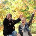 vrolijke paar spelen met dode bladeren in de herfst — Stockfoto