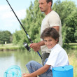 Father and son fishing at a lake — Stock Photo