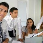 Businessteam gathered around desk — Stock Photo