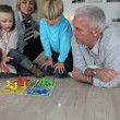 Couple playing a board game with their grandchildren — Stock Photo