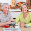 Two old women playing chess in kitchen — Stock Photo
