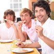 Three friends enjoying outdoor meal together — Stock Photo