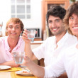 Stock Photo: Three young men eating meal together and drinking water