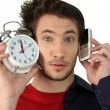 Man holding alarm clock and mobile telephone — Photo
