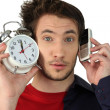 Man holding alarm clock and mobile telephone — Stock Photo