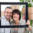 A couple is holding and posing behind a painting frame inside an apartment — Stock Photo