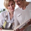 Stock Photo: Couple looking at cookery book
