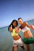 Thumbs up from friends at the beach — Stock Photo