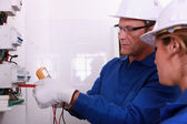 Electricians fitting a fusebox — Stock Photo