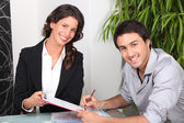 Female real estate agent and young man buying house — Stock Photo
