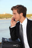 Young man talking on phone outdoors — Stock Photo