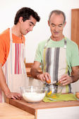Senior and junior cooking together — Stock Photo