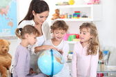 A woman and three little girls watching a globe — Stock Photo