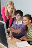 Three young looking at a computer — Stock Photo