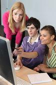 Three young looking at a computer — Stock Photo
