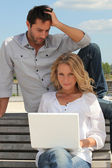 Couple with laptop outdoors — Stock Photo