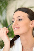 Woman applying eyeliner — Stock Photo