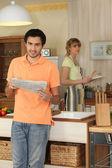 Genç adam karısını yemek pişiriyor iken bir gazete okuyor — Stok fotoğraf