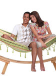 Happy couple sitting in a hammock — Stock Photo