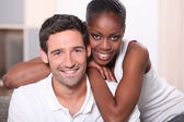 Landscape portrait of a mixed race couple indoors — Stock Photo