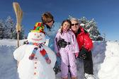 Family stood by snowman — Stock Photo