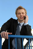 Young businessman speaking on his mobile phone outdoors — Stock Photo