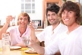 Three young men eating a meal together and drinking water — Stock Photo