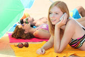 Girl sunbathing and talking on the phone — Stock Photo
