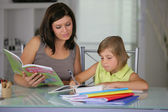 Mother helping daughter with schoolwork — Stock Photo