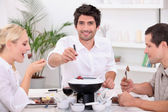 Friends enjoying chocolate fondue — Stock Photo