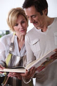 Couple looking at cookery book — Stock Photo