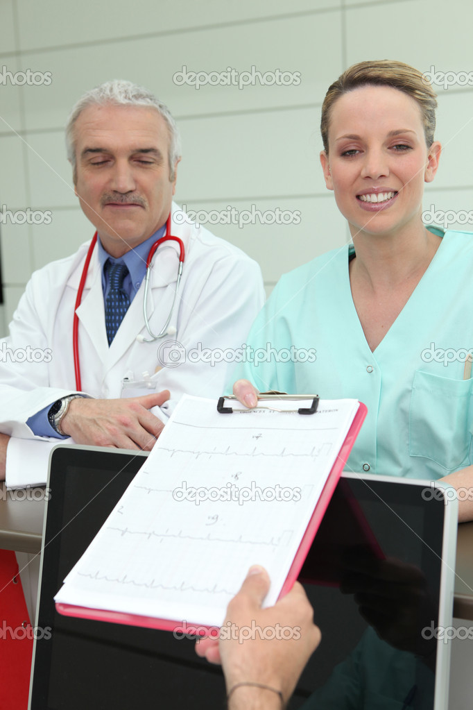 Doctor and nurse with a clipboard at reception — Stok fotoğraf #8926807