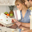 Young couple using a cookbook — Stock Photo #8930021