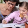 Woman helping her granddaughter with her homework — Stock Photo #8930315