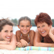 A 30 years old woman, a little girl and a 55 years old woman lying down on — Stock Photo