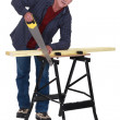 Stock Photo: Tradesmsawing wooden plank