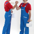 Two decorators greeting each other - Stock Photo