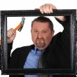 Businessman with a hammer and frame — Stock Photo #8930840