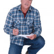 Stock Photo: Builder writing on piece of paper