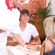 Young couple eating pizza in a restaurant — Stock Photo